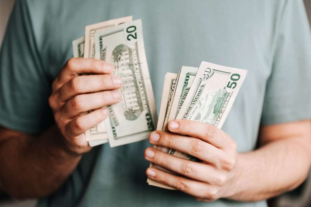 Hands holding money brought in from LinkedIn ads