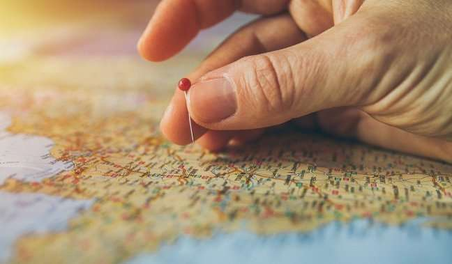 Hand putting a pin in a map to represent goals