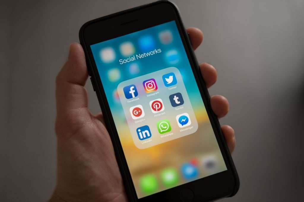 Hand holding phone and using PPC to increase social media followers