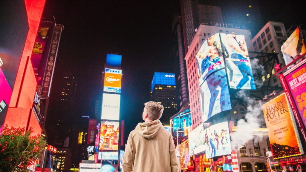 Young man looking up at bright New York City ads, programmatic advertising