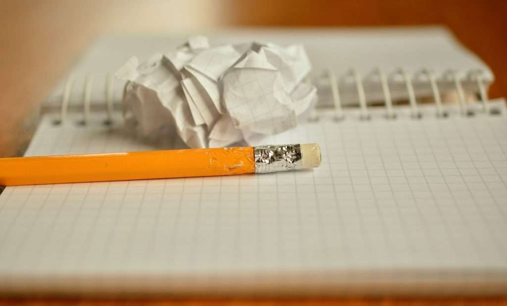 Closeup of pencil laying in an open notebook next to crumpled paper.