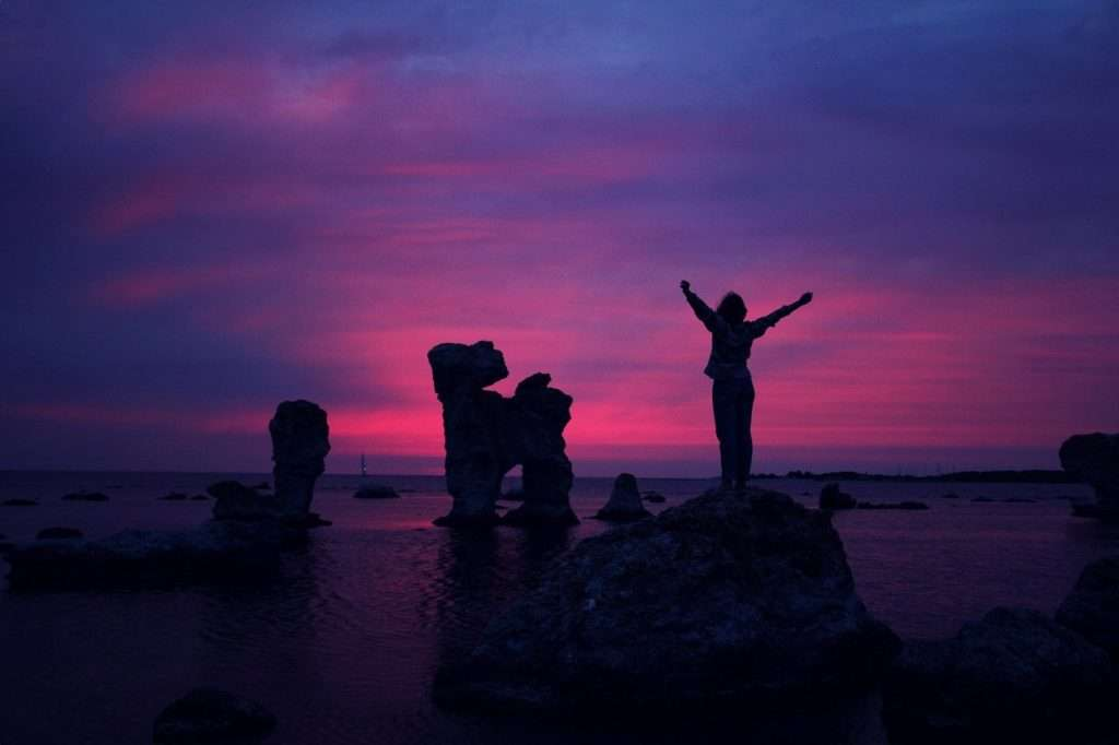 Silhouettes of rocks and a person with raised arms on a beach at sunset.